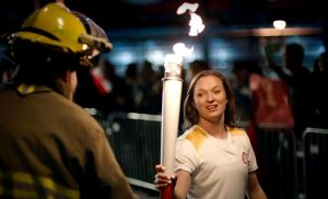 Firefighter handing the Olympic torch to a woman