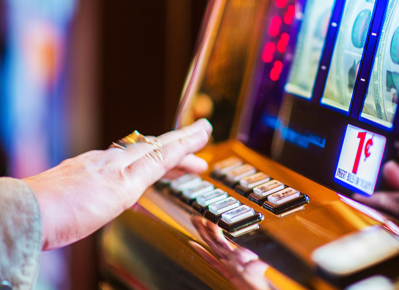 Older person playing the 1 cent slot machine at a casino