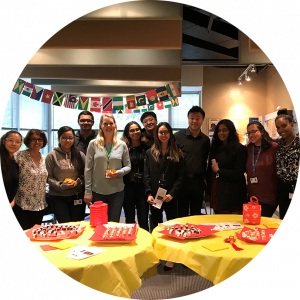 OLG employees standing behind two yellow round tables with snacks in celebration of diversity.