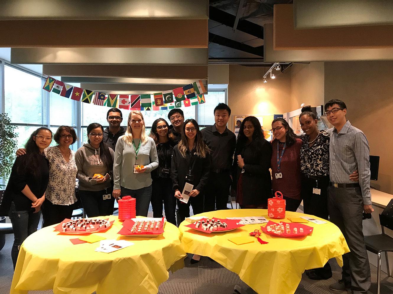 Employés d'OLG derrière deux tables jaunes offrant des collations pour célébrer la diversité.