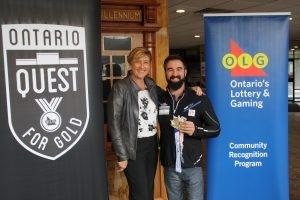 Man and woman standing between OLG banner and Ontario quest for gold banner while the man holding a gold medal.