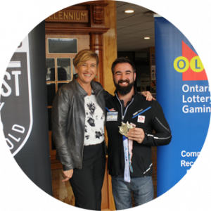 Man and woman standing between OLG banner and Ontario quest for gold banner while the man holds a gold medal.