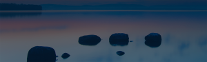 4 rocks on Lake Superior with the water reflecting the skies while the sun sets in the background.