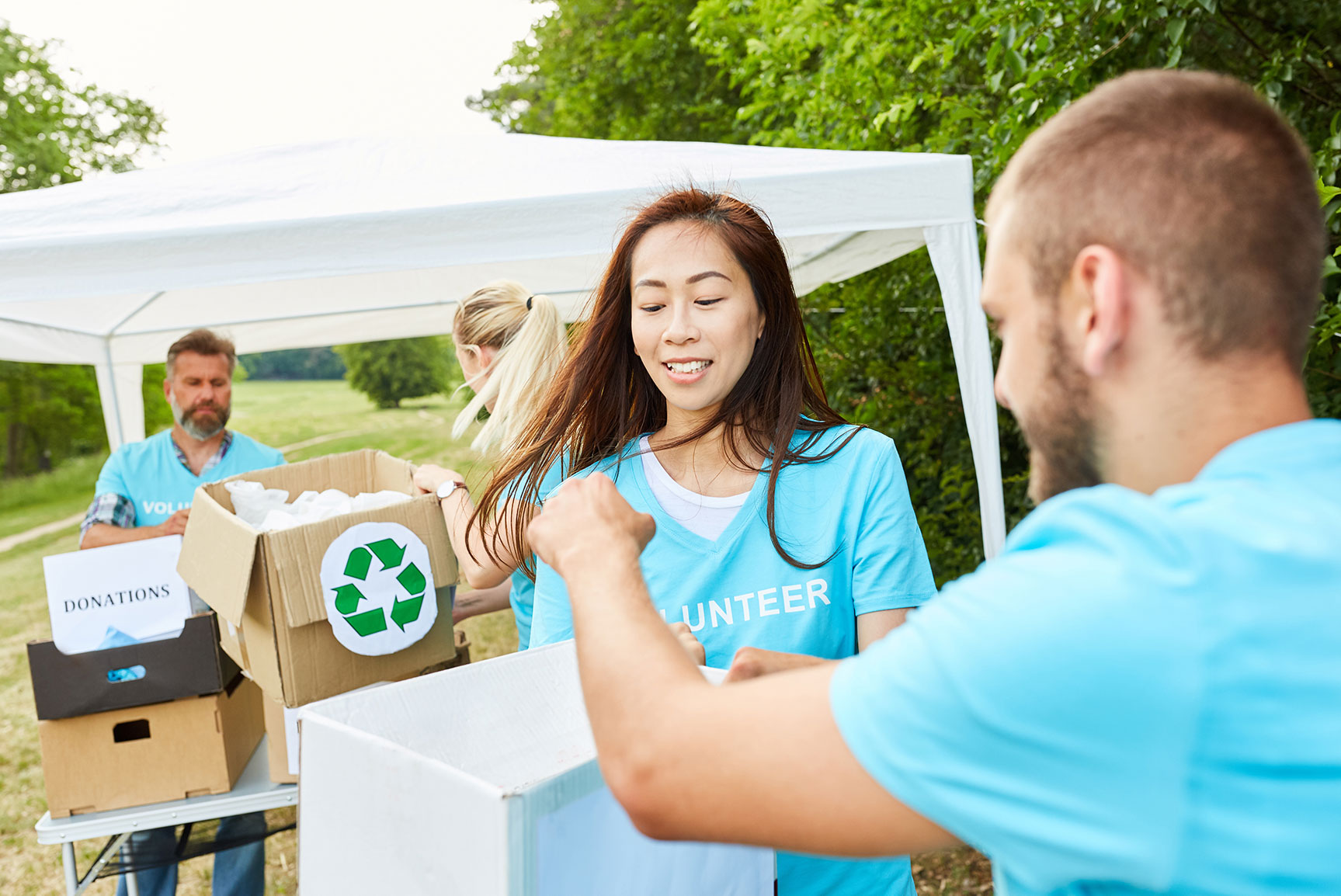Deux hommes et deux femmes portant des t-shirts bleus de bénévoles lors d'un événement.