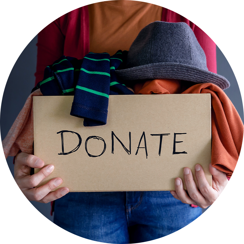 Person holding a donation box full of donated clothing.
