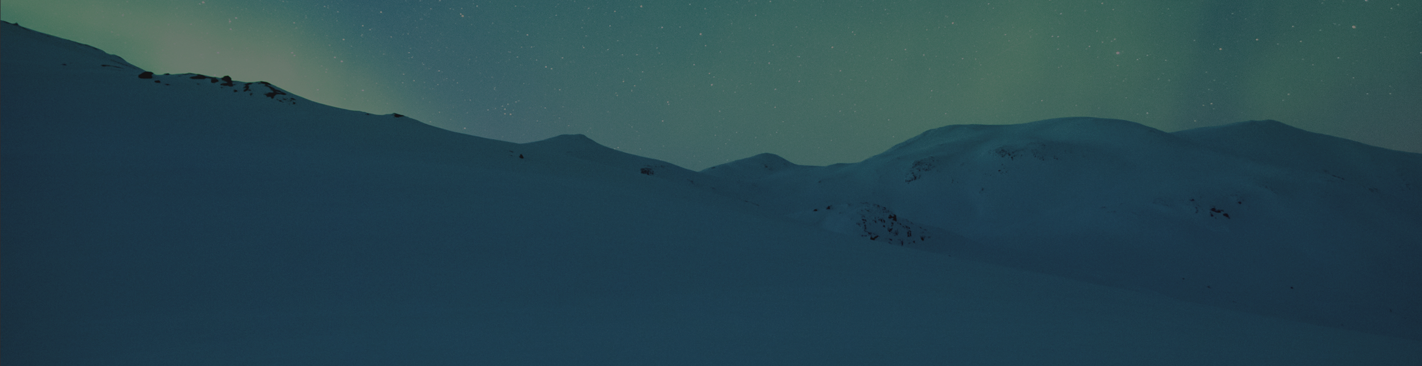 Snow-covered mountain slopes with the northern lights in the background.