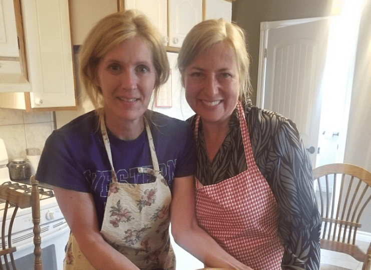 Two OLG employees in a kitchen, wearing aprons and smiling.