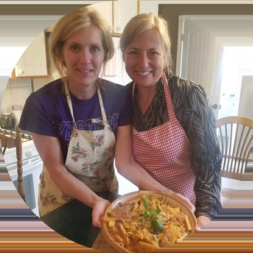 Deux employées d'OLG portant des tabliers tiennent un plat qu'elles ont cuisiné.