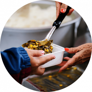 A pair of hands giving out food at a soup kitchen while another hand receives it in a white container.
