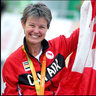 La paracycliste de compétition Shelley Gautier, tenant un drapeau canadien lors des Jeux olympiques de Rio 2016.